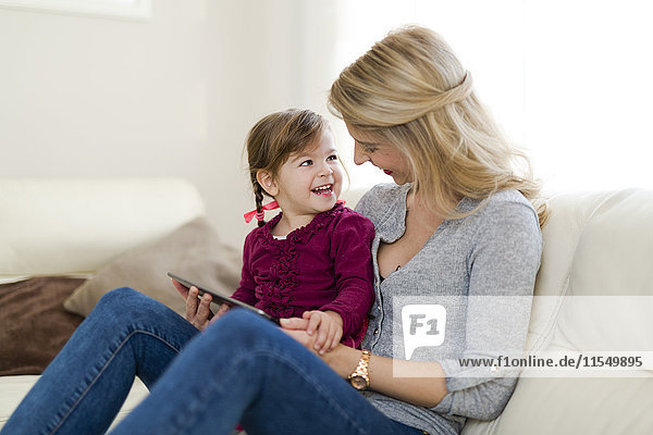 Mother and her little daughter sitting on couch in the living room with digital tablet