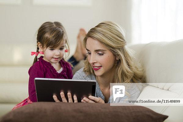 Mutter und ihre kleine Tochter zusammen auf der Couch im Wohnzimmer mit Blick auf das digitale Tablett