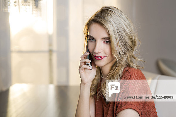 Portrait of smiling blond woman sitting on couch in the living room telephoning with her smartphone