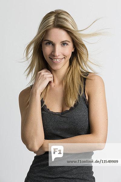 Porträt einer lächelnden blonden Frau mit wehendem Haar
