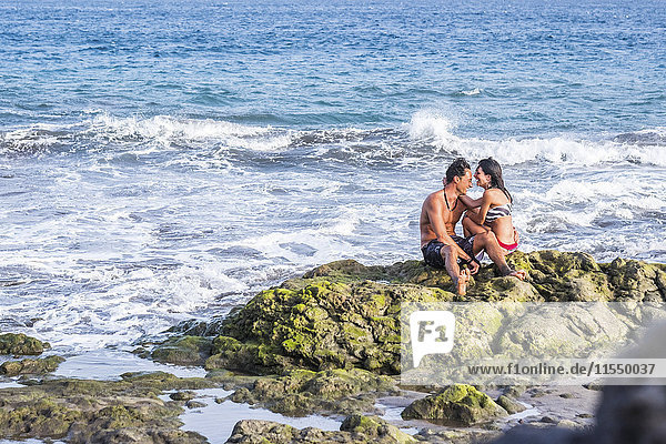 Happy couple in love sitting on rock in the sea