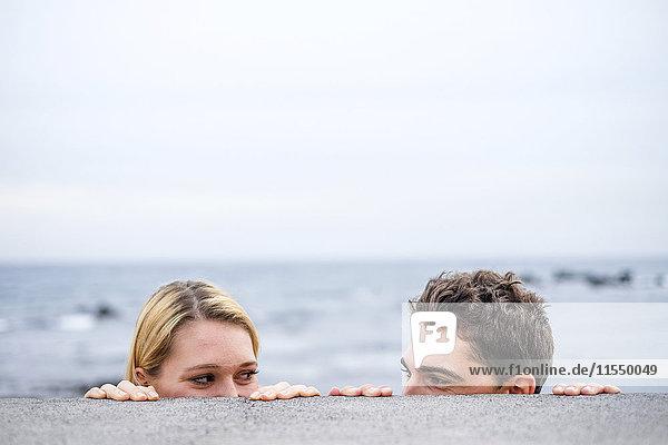 Verspieltes junges Paar  das sich hinter einer Wand ansieht.