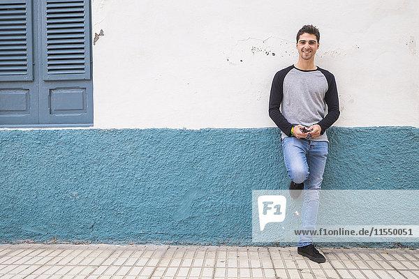 Lächelnder junger Mann  der sich an eine Wand lehnt. Lächelnder junger Mann, der sich an eine Wand lehnt.
