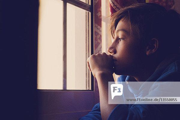 Nachdenklicher Junge schaut durchs Fenster