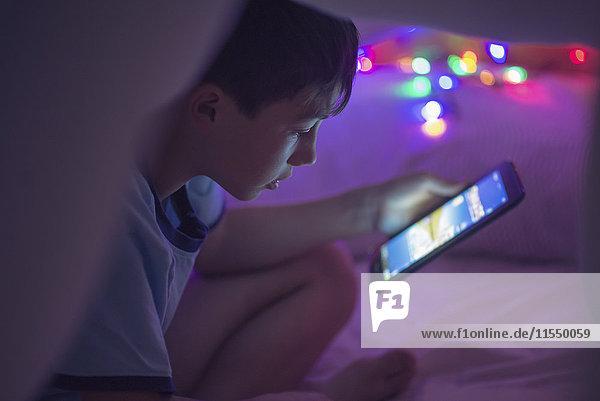 Junge sitzt unter einer Decke und schaut auf die digitale Decke. Junge sitzt unter einer Decke und schaut auf die digitale Decke.
