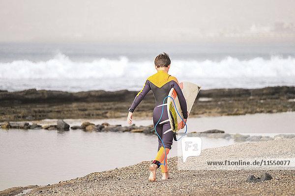 Spanien  Teneriffa  Junge mit Surfbrett am Strand spazieren gehen