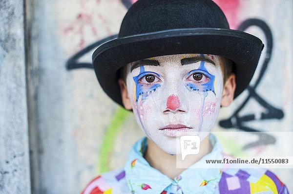 Porträt eines traurigen Jungen  der als Clown gekleidet ist.