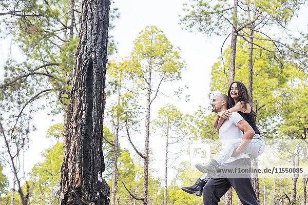 Spanien  Teneriffa  glücklicher Mann  der seiner Freundin eine Huckepackfahrt im Teide-Nationalpark anbietet.