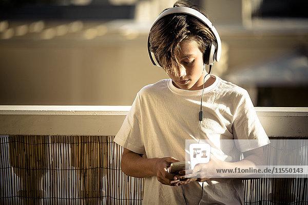 Junge hört Musik mit Kopfhörer und Smartphone auf dem Balkon