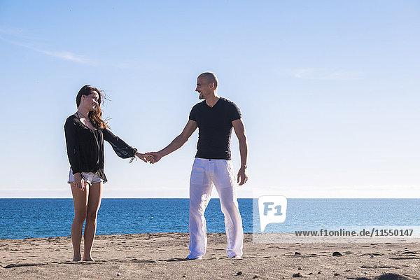 Spanien  Teneriffa  das glückliche Paar steht Hand in Hand am Strand