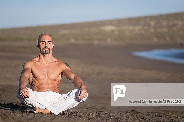 Spanien  Teneriffa  Mann beim Meditieren am Strand