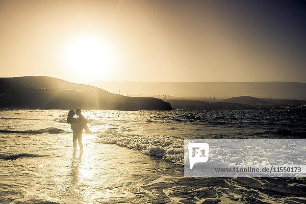 Spanien  Teneriffa  Silhouette eines jungen verliebten Paares am Meer