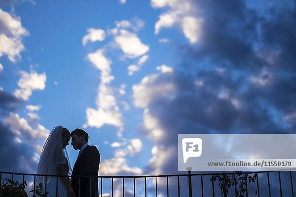 Silhouette of young bridal couple standing face to face in front of a cloudy sky