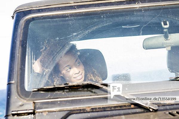 Spanien  Teneriffa  lächelnde Frau in einem Auto sitzend  etwas beobachtend