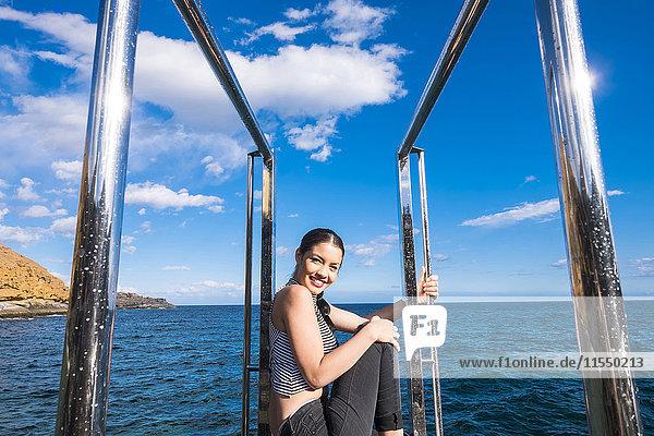Spanien  Teneriffa  Portrait einer lächelnden jungen Frau  die auf einer Plattform vor dem Meer sitzt.