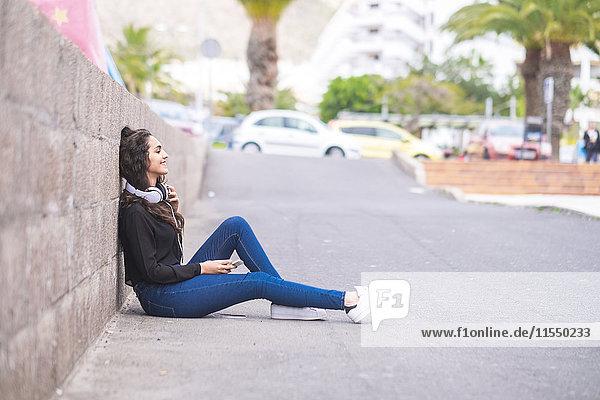Spanien  Teneriffa  lächelndes Teenagermädchen mit Kopfhörer und Smartphone auf dem Boden sitzend Spanien, Teneriffa, lächelndes Teenagermädchen mit Kopfhörer und Smartphone auf dem Boden sitzend
