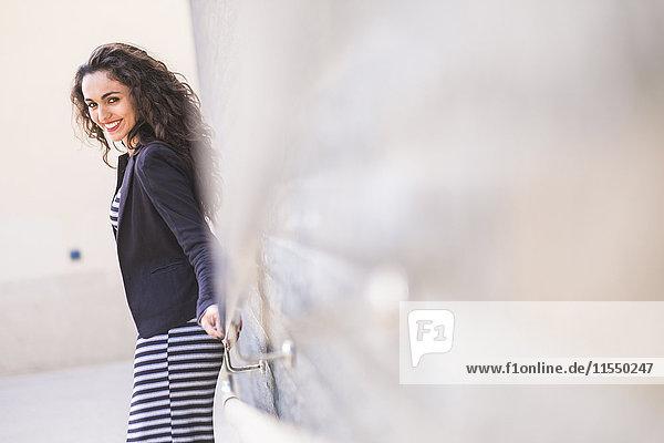 Porträt eines lächelnden Teenagermädchens  das sich an eine Wand lehnt.