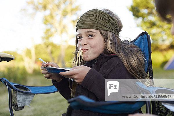 Mädchen beim Spaghettiessen auf dem Campingplatz