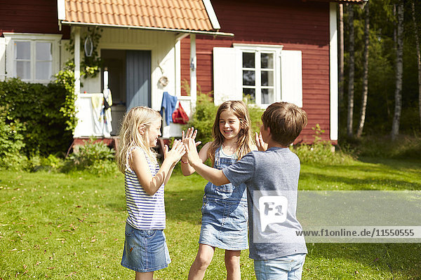 Schweden  drei Kinder spielen auf einer Wiese vor dem Ferienhaus