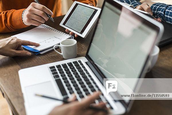 Kollegen am Schreibtisch mit digitalem Tablett  Laptop und Notizblock