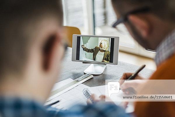 Kollegen im Büro sehen sich einen Videofilm auf einem digitalen Tablett an.