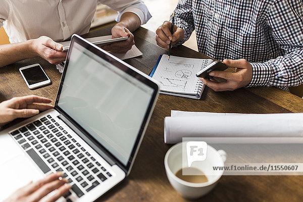 Kollegen am Schreibtisch mit Smartphone  Laptop und Notizblock