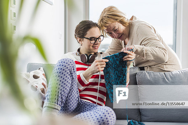 Young woman sitting on couch showing knitwear to senior woman