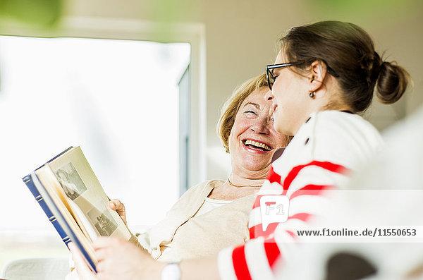 Glückliche Seniorin und junge Frau auf der Couch beim Betrachten des Fotoalbums