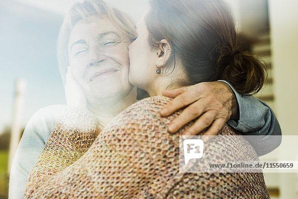 Junge Frau küsst ältere Frau hinter Fensterscheibe