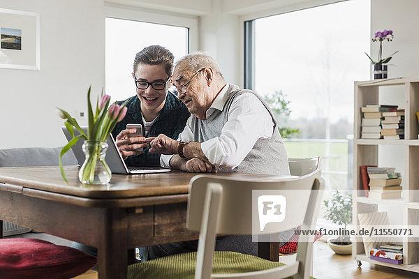 Senior Mann und sein Enkel sitzen am Tisch im Wohnzimmer mit Laptop und Smartphone