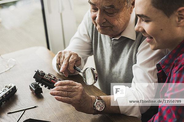 Senior und Enkel mit Spielzeugeisenbahn zu Hause