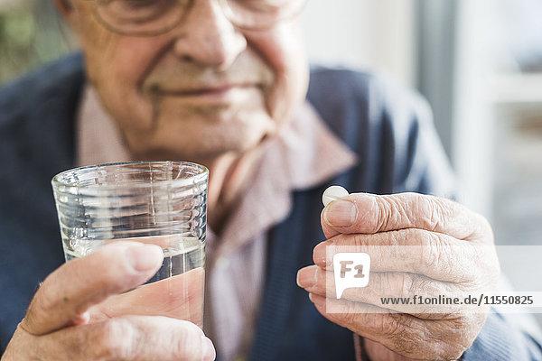 Hände des älteren Mannes halten Tablette und Glas Wasser  Nahaufnahme