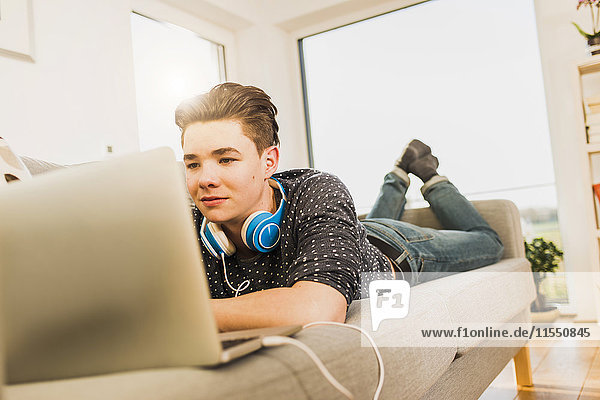 Junger Mann auf der Couch liegend mit Laptop