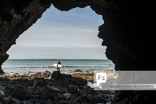 Frankreich  Bretagne  Finistere  Halbinsel Crozon  Mann am Felsenstrand mit Surfbrett