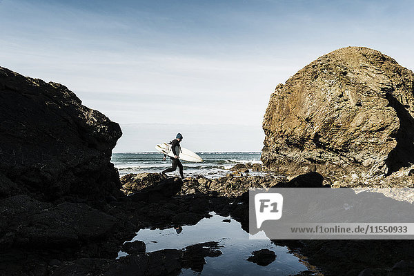 Frankreich  Bretagne  Finistere  Halbinsel Crozon  Mann  der am felsigen Strand mit Surfbrett läuft
