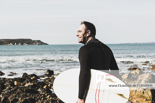 Frankreich,  Bretagne,  Finistere,  Halbinsel Crozon,  lächelnder Mann am Felsenstrand mit Surfbrett