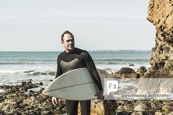 Frankreich  Bretagne  Finistere  Halbinsel Crozon  selbstbewusster Mann am Felsenstrand mit Surfbrett
