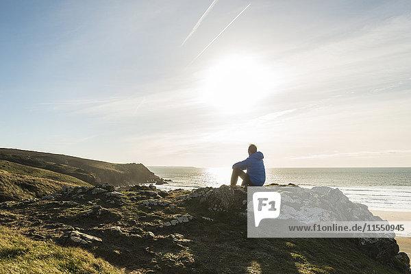 Frankreich  Bretagne  Finistere  Halbinsel Crozon  Mann auf Felsen an der Küste sitzend
