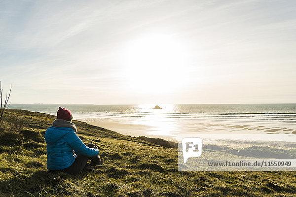 France  Bretagne  Finistere  Crozon peninsula  woman sitting at the coast at sunset