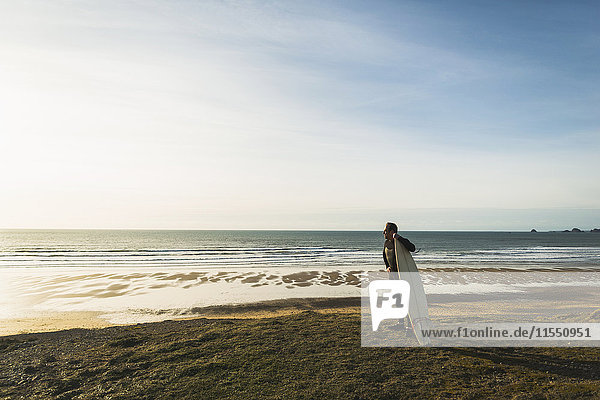 Frankreich  Bretagne  Finistere  Halbinsel Crozon  Mann an der Küste stehend mit Surfbrett