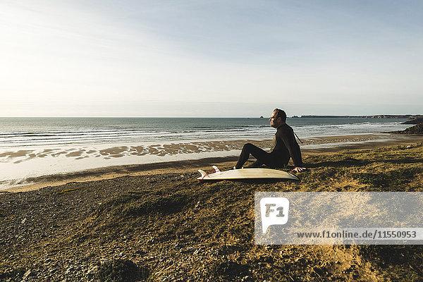 Frankreich  Bretagne  Finistere  Halbinsel Crozon  Mann an der Küste sitzend mit Surfbrett