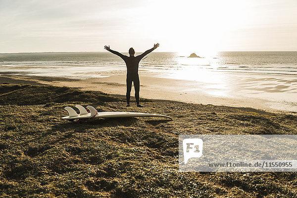 Frankreich  Bretagne  Finistere  Halbinsel Crozon  Mann an der Küste mit ausgestreckten Armen und Surfbrett