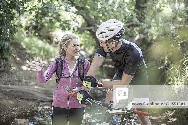 Mann auf dem Mountainbike im Wald im Gespräch mit Frau