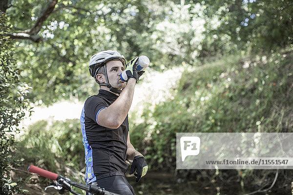 Mann auf dem Mountainbike im Wald Trinkwasser