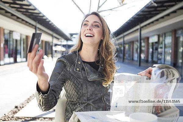 Junge Frau sitzt im Cafe und bezahlt mit Kreditkarte