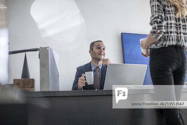 Geschäftsmann am Schreibtisch mit Tasse Kaffee und Blick auf den Kollegen