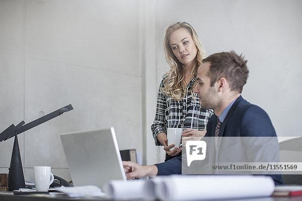 Geschäftsmann am Schreibtisch mit Kollegen beim Blick auf den Laptop