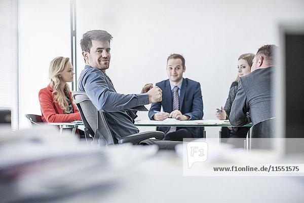 Lächelnder Geschäftsmann bei einer Besprechung im Konferenzraum