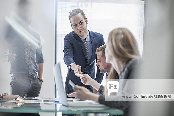 Geschäftsmann übergibt Brief an Kollegen während einer Besprechung im Konferenzraum