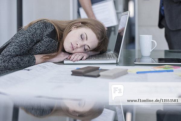 Frau schläft auf dem Tisch im Büro